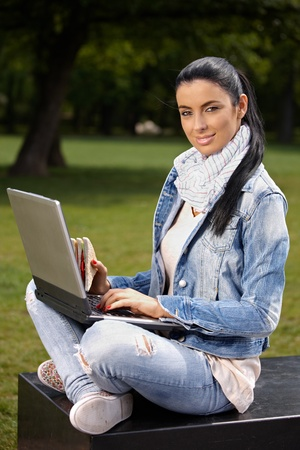 Attractive woman with laptop and sandwitch sitting in park, looking at camera. photo