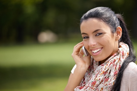 Pretty girl talking on mobile phone in park, smiling at camera. photo