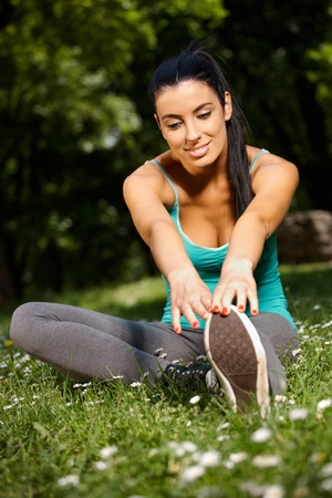 Smiling young woman stretching in park in sportswear. photo