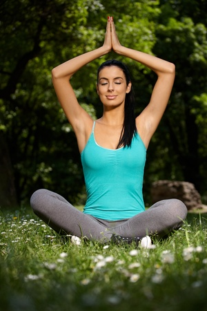 Beautiful young woman meditating eyes closed in yoga pose in park. photo
