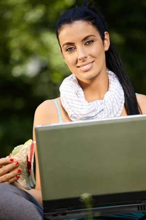 sandwitch: Lunchtime portrait of young woman with laptop and sandwitch.