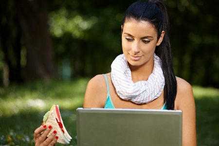 lunchtime: Young woman in park at lunchtime, using laptop, eating club sandwich. Stock Photo
