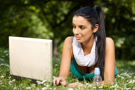 citypark: Pretty girl laying in grass in citypark, browsing internet, looking at screen.