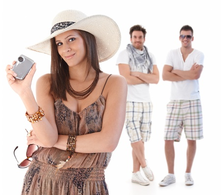 Portrait of smiling young woman in summer dress holding compact camera, handsome men standing behind.%uFFFD photo