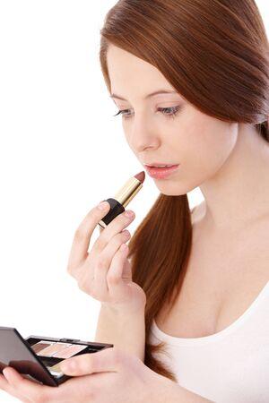 gingerish: Adolescente gingerish poner l�piz labial, buscando a s� misma en espejo. Foto de archivo