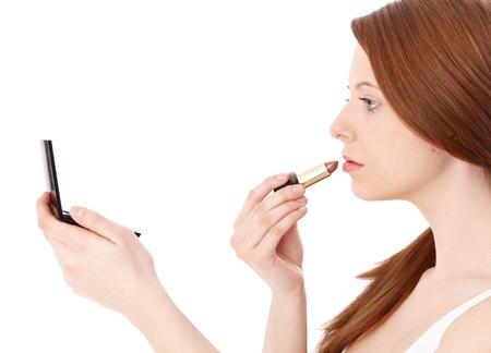 gingerish: Ginger girl putting on lipstick, using mirror, side view.