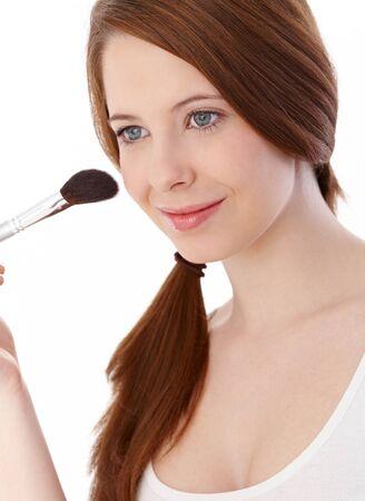 gingerish: Beautiful ginger girl applying makeup with brush, smiling, looking away. Stock Photo