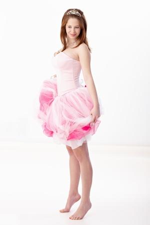 stockphoto: Young gingerish woman posing on tiptoe, wearing pink evening dress, smiling.