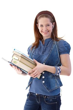 single songs: Happy schoolgirl smiling with books in hands, using headset.