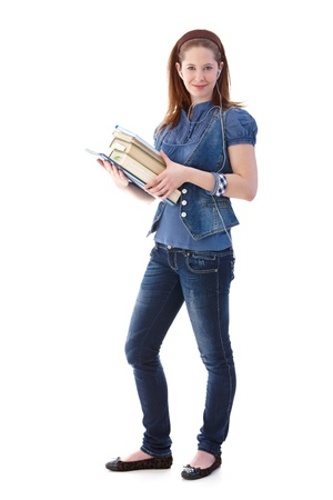 Young girl standing with books in hands, smiling, full length. photo