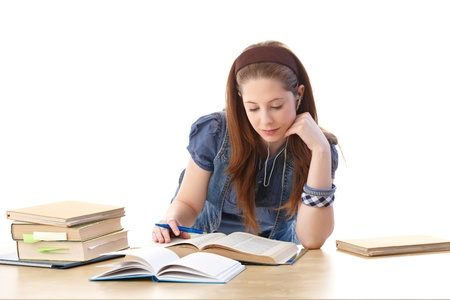 Young girl sitting at desk at home, doing homework, looking at books. photo