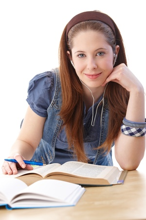 College student sitting at desk, learning, smiling at camera. photo