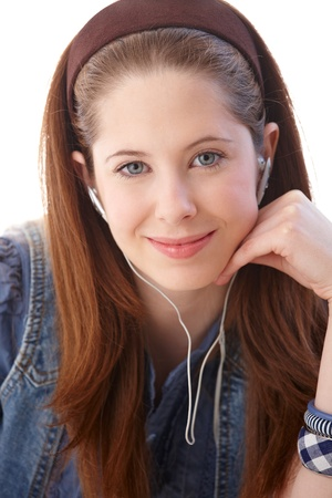 Closeup portrait of young ginger girl, smiling, listening to music through headphones. photo