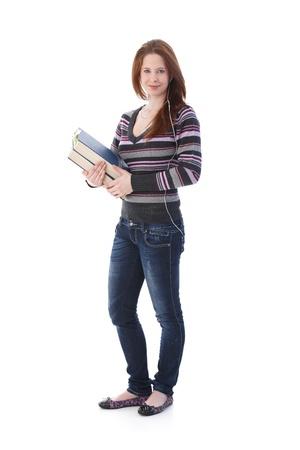 highschool: Pretty schoolgirl holding books in hands, listening music through headphones.