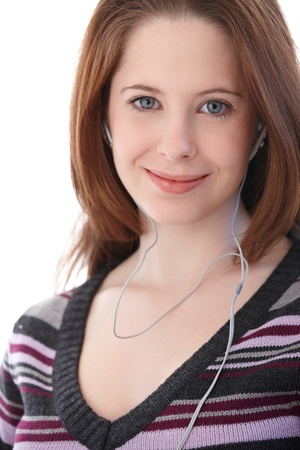 Portrait of young woman listening music through headphones, smiling. photo