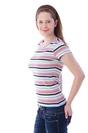 one teenage girl only: Atractiva joven posando en camiseta y pantalones vaqueros, sonriendo.