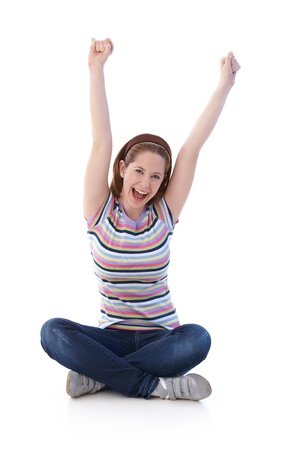 upraised: Young girl sitting on floor in tailor seat, stretching hands towards the sky, shouting happily.