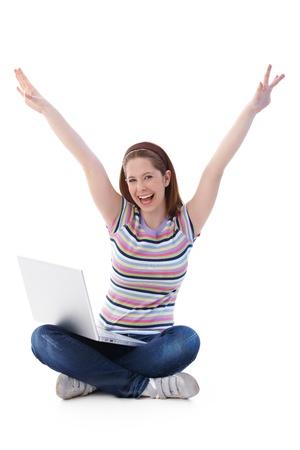 one teenage girl only: Linda chica sentada en el suelo en asiento de sastre, gritando alegremente con manos alzados.