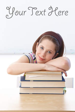 Pretty schoolgirl laying on books, sitting at desk in classroom front of whiteboard. Stock Photo - 9562424