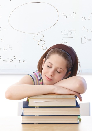 Young girl sleeping on books, sitting at desk in classroom, dreaming. photo