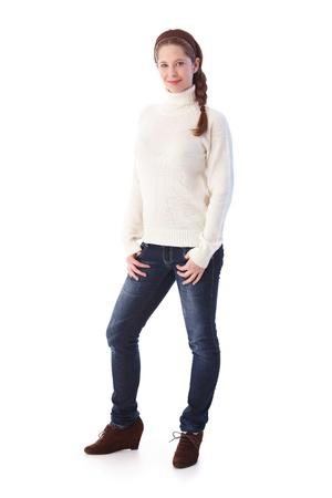 Muy joven en jeans y suéter sonriendo a la cámara. Foto de archivo