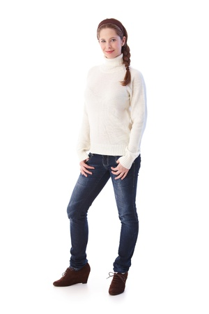 Pretty young girl in jeans and sweater smiling at camera.