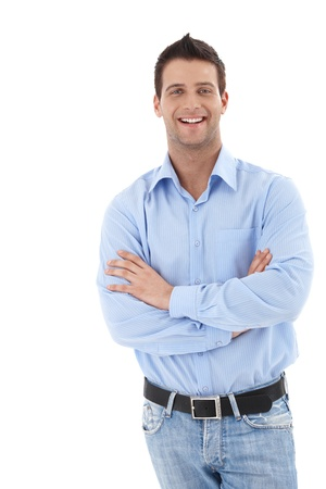 one young man only: Laughing young businessman in casual clothing, standing with arms crossed, looking at camera. Stock Photo