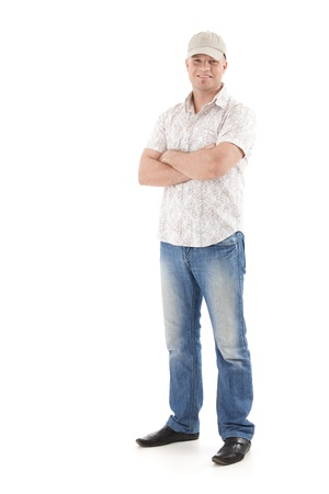 folded arms: Casual summer portrait of young man wearing baseball hat, smiling, standing with arms folded, isolated on white. Stock Photo