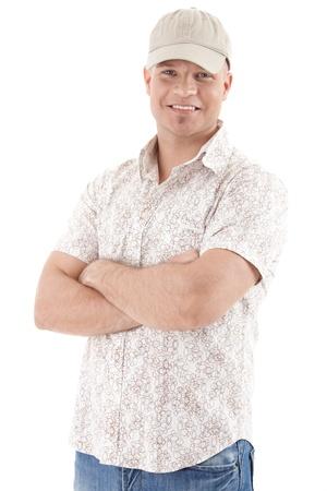 casquette: Handsome guy dans la casquette de base-ball souriant � la cam�ra, portant des v�tements casual, bras repli�s, isol� sur fond blanc.