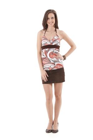 mini jupe: Jolie femme posant en studio dans des v�tements d'�t� et mini jupe, en souriant � la cam�ra, isol� sur fond blanc, pleine longueur. Banque d'images