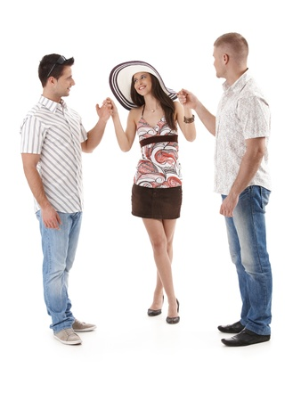 Pretty woman in mini skirt and straw hat standing with two men in summer shirt, holding hand, smiling, cutout on white. photo