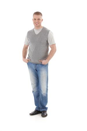 persona de pie: Retrato casual de guy de estudiante de la Universidad Permanente con las manos en el bolsillo, sonriendo a la c�mara, aislado en tama�o completo blanco.