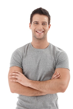 folded arms: Casual portrait of happy university student guy standing with arms folded, laughing. Stock Photo
