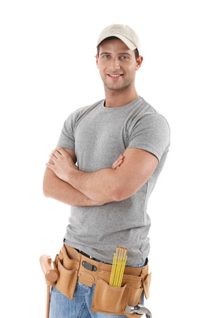 bel homme: Beau bricoleur dans les commandes de chapeau de baseball avec les bras repli�s, sourire � la cam�ra, d�coupage sur fond blanc.
