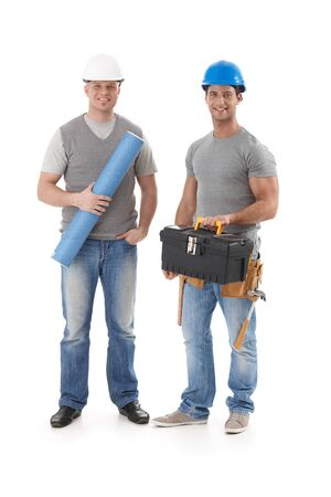 Happy engineer and builder workman standing with tools and floor plan, smiling at camera, isolated on white. Stock Photo - 9562749