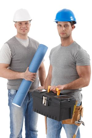 Athletic contractor standing holding toolset, engineer guy holding floor plan, wearing hardhat, smiling at camera, isolated on white. Stock Photo - 9564411
