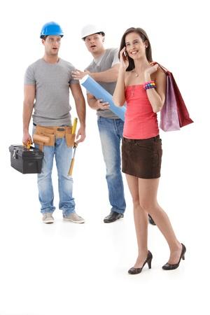 minijupe: Travailleurs Builder fixement belle femme en mini jupe et des talons hauts marche par, souriant. Isol� sur fond blanc.