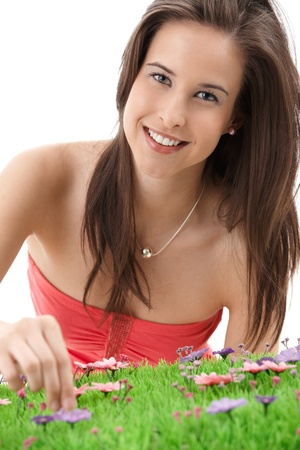 Pretty girl picking flowers, smiling at camera, isolated on white. photo