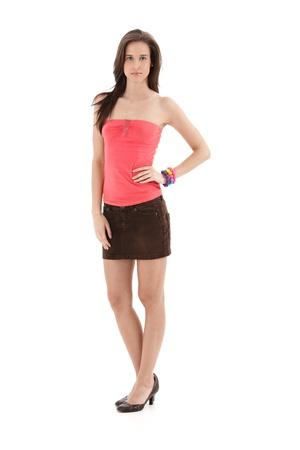 mini jupe: Jolie fille posant en studio dans des v�tements d'�t� � la mode mini-jupe et talons hauts, isol� sur blanc, pleine longueur. .