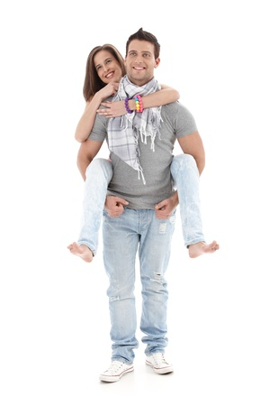 Portrait of goodlooking boyfriend carrying girl on back, laughing, having fun, isolated on white, full size. photo