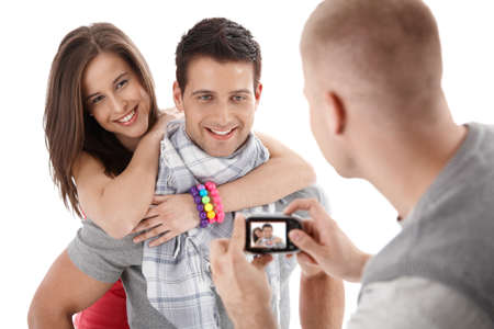 Friend taking photo of happy couple smiling and hugging, isolated on white. photo