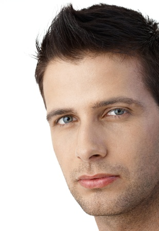one young man only: Closeup facial portrait of determined goodlooking man looking at camera.