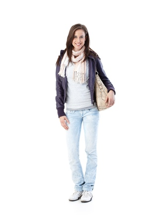 Portrait of pretty trendy young woman, college student, standing in jacket holding handbag, smiling at camera, isolated on white, full length. Stock Photo - 9562330