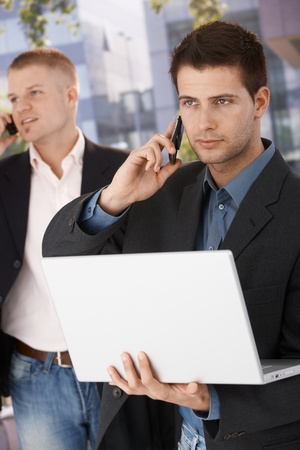 Two businessmen busy making phone call, using mobile, holding laptop computer, standing outside of office. photo