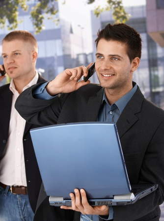 Businessmen using mobile phone, smiling, standing outside of office with laptop computer. photo