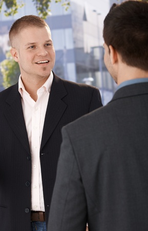 Two businessmen meeting outside of office building, smiling. photo