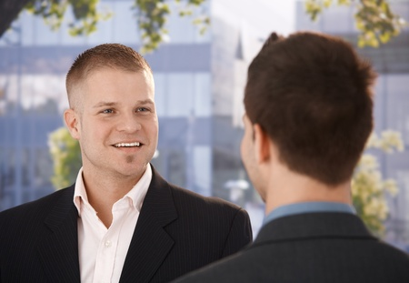 talking businessman: Businessmen chatting outside of office, businessman smiling at colleague.