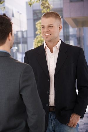 Businesspeople talking at office building, businessman smiling at coworker. photo