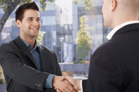 Businessmen shaking hands in front of office building, smiling. photo