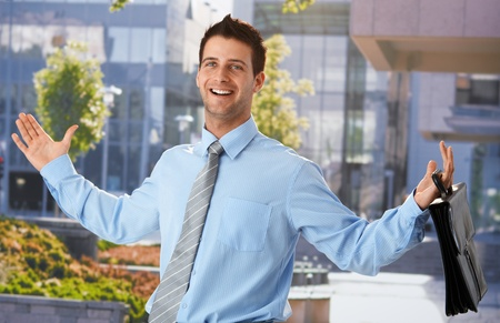 leave: Happy businessman standing outside office, leaving from work, arms wide open, holding briefcase, smiling. Stock Photo